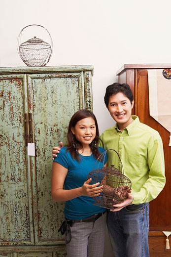Portrait of a young couple holding a cage and smiling : Stock Photo
