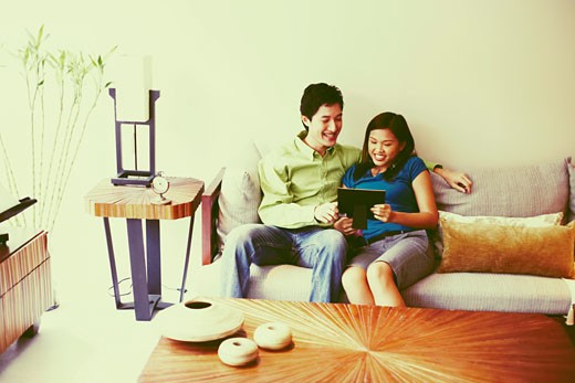 Young couple looking at a picture frame and smiling on a couch : Stock Photo