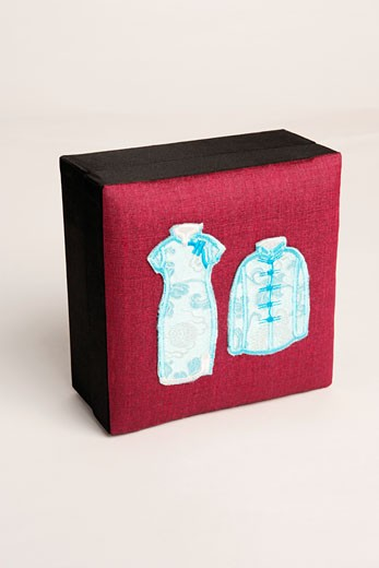 Close-up of traditional Chinese outfits embroidered on a box : Stock Photo