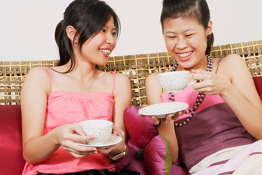 Close-up of two young women sitting on a couch and holding tea cups : Stock Photo