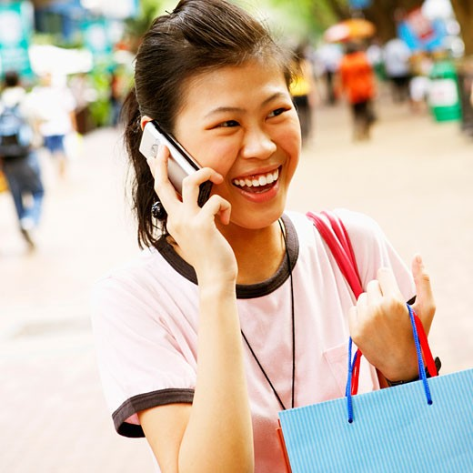 Close-up of a young woman talking on a mobile phone and carrying a shopping bag : Stock Photo