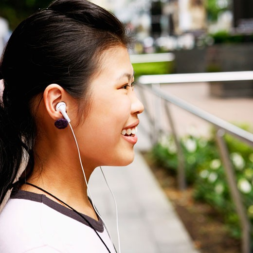 Side profile of a young woman wearing headphones and listening to music : Stock Photo