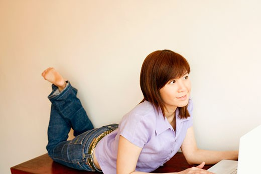 Stock Photo: 1768R-7651 Close-up of a young woman lying on a table and using a laptop