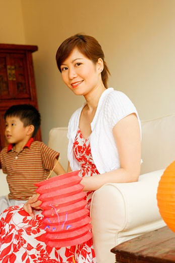 Portrait of a young woman holding a Chinese lantern with her son beside her : Stock Photo