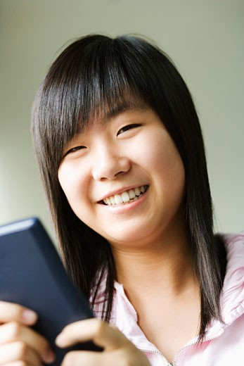 Stock Photo: 1768R-8009 Portrait of a girl holding a video game and smiling