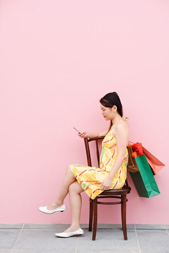 Stock Photo: 1768R-8133 Side profile of a young woman sitting on a chair and using a mobile phone