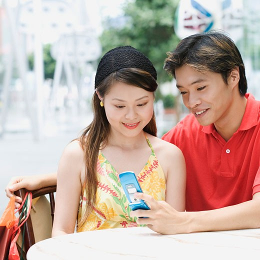 Close-up of a young couple sitting in a cafeteria and looking at mobile phone : Stock Photo