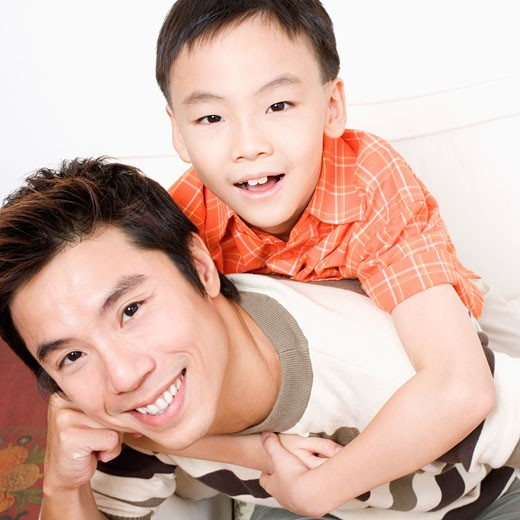Portrait of a boy riding piggyback on his father : Stock Photo