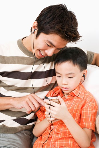 Stock Photo: 1768R-8389 Close-up of a mid adult man and his son listening to an MP3 player