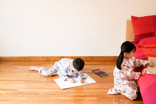High angle view of a girl and boy drawing on paper : Stock Photo