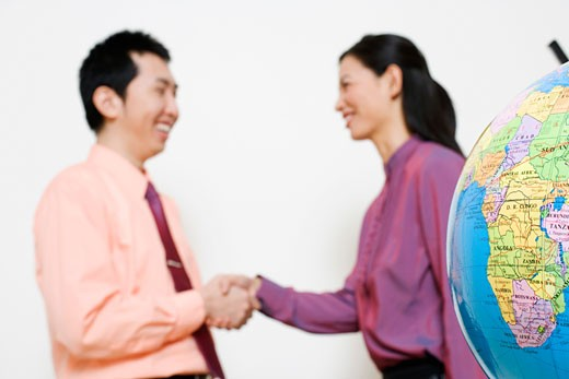 Businesswoman shaking hands with a businessman : Stock Photo