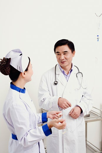 Male doctor talking to a female nurse : Stock Photo