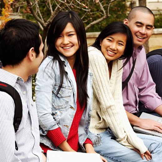 Four college students sitting in a college campus and smiling : Stock Photo