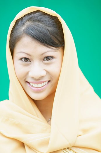 Portrait of a young woman wearing a scarf smiling : Stock Photo