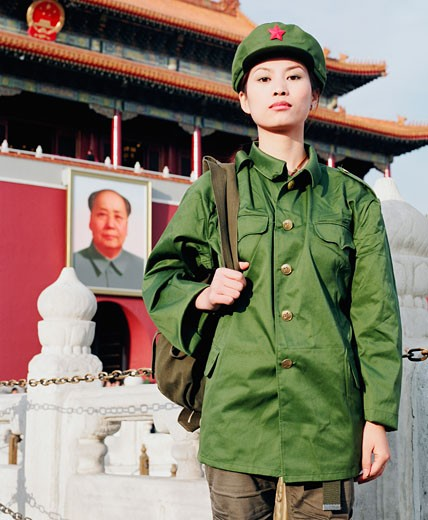 Portrait of a young woman in army uniform standing in front of a palace, Forbidden Palace, Beijing, China : Stock Photo