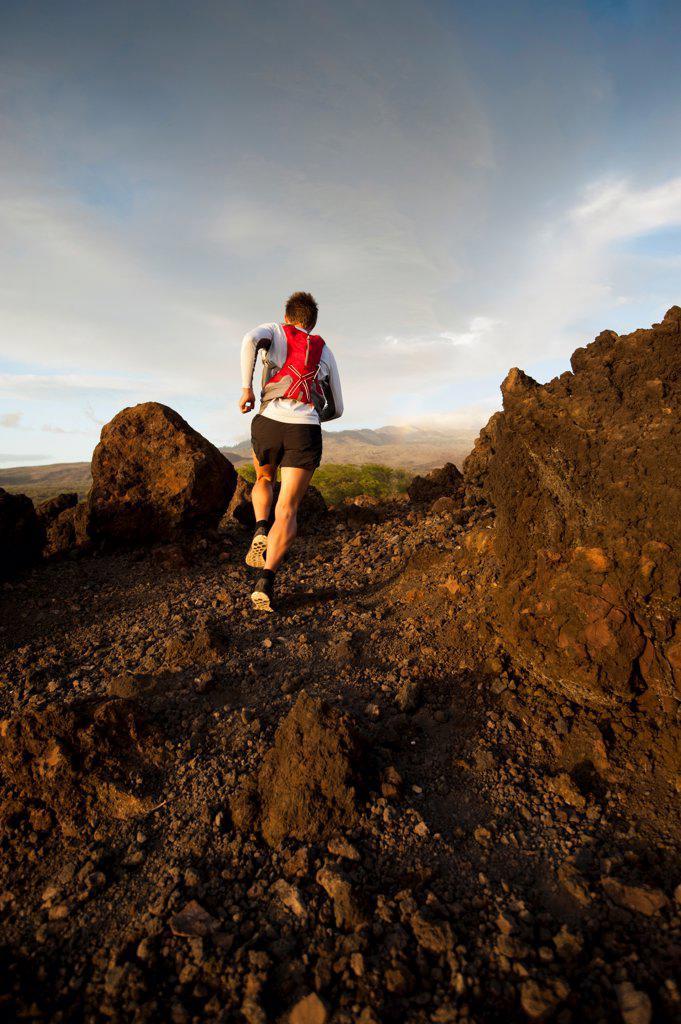 Man running on rocky rural trail : Stock Photo