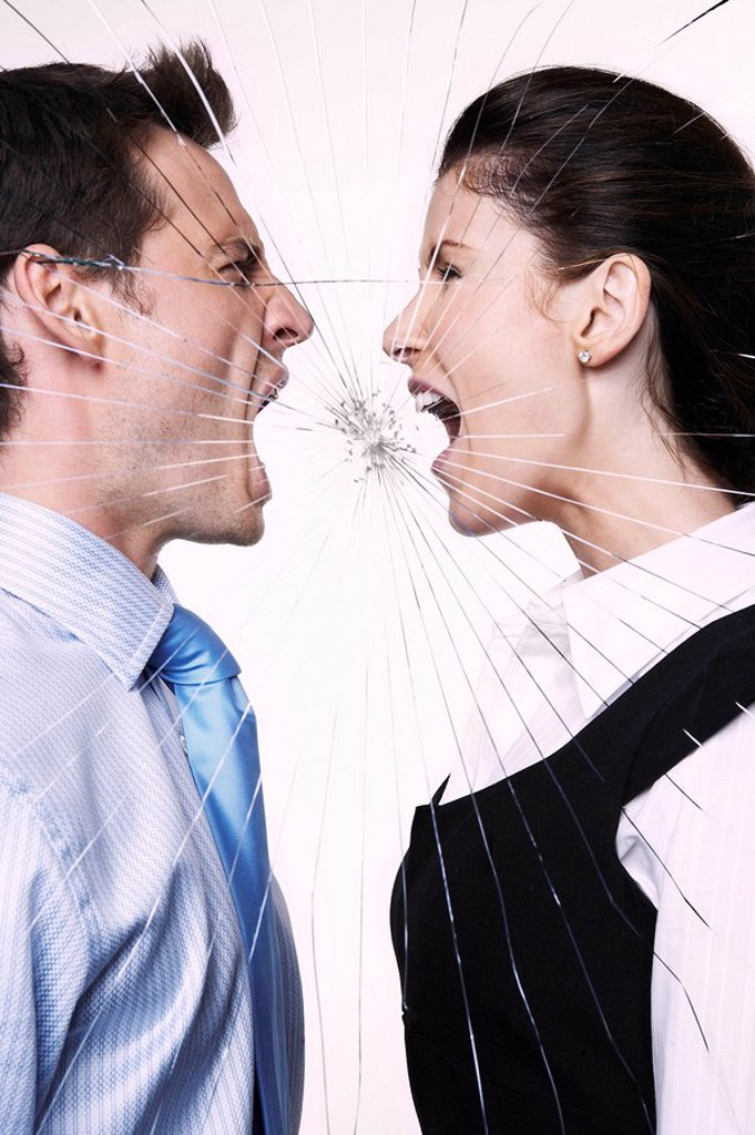Young man and woman behind cracked glass shouting at each other : Stock Photo