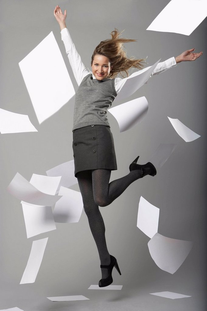 young business woman jumping with flying sheets of A4 white office paper : Stock Photo
