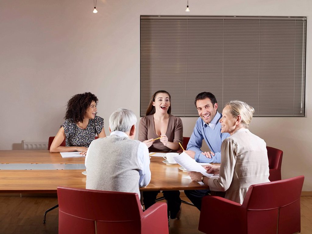 Stock Photo: 1773-20363 Group of people sitting around conference table having a meeting. They are all laughing and listening to an senior woman talking.