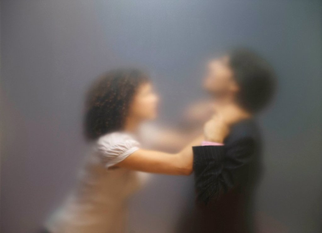 Blurred image of woman trying to strangle co_worker. Seen through frosted office screen. : Stock Photo