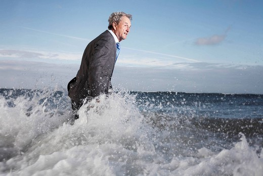 a businessman wading into the sea : Stock Photo