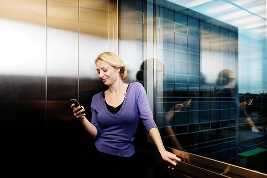 Woman in elevator, with cellular phone : Stock Photo
