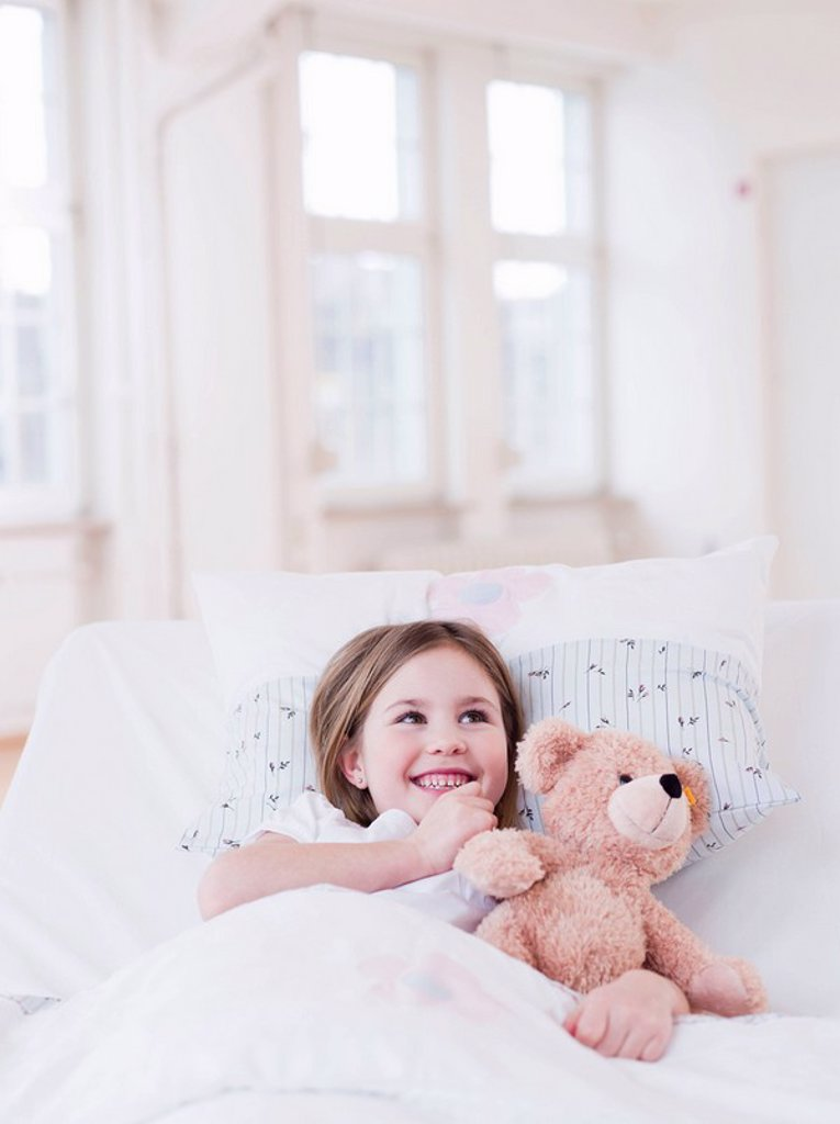 Stock Photo: 1773-20939 A young girl with brown hair lying in bed, a teddy bear in her arms, smiling