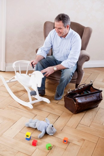 Man in casual clothes sitting in a chair repairing toys : Stock Photo