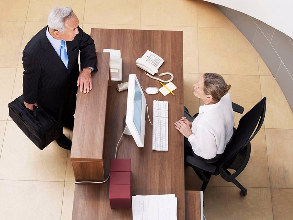 Stock Photo: 1773-21165 Female receptionist talking to senior businessman. Seen from above.