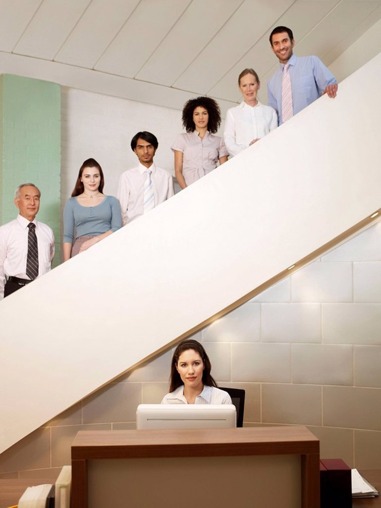 Stock Photo: 1773-21179 Six office workers of different ages posing on staircase behind a receptionist