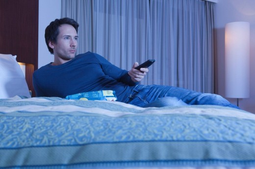 man on hotel bed watching TV : Stock Photo