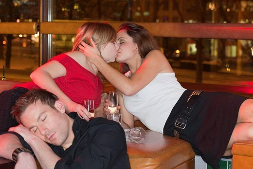 two women kissing, boy asleep in foreground : Stock Photo