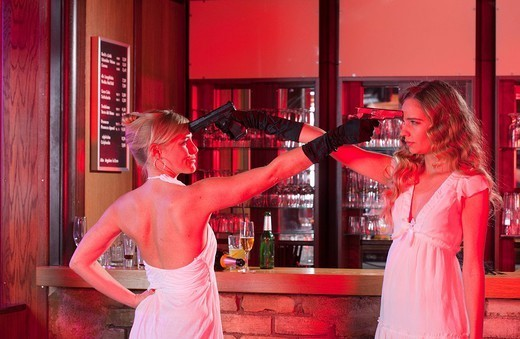 two girls at bar with plastic guns : Stock Photo