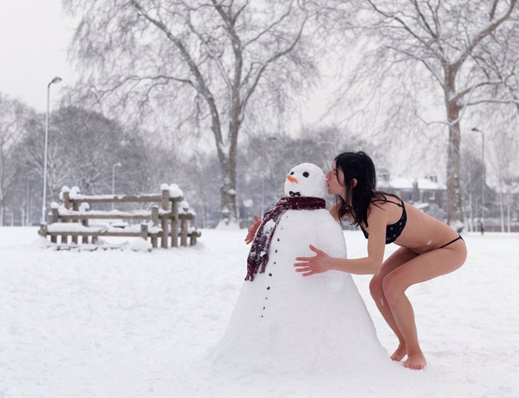Woman in bikini kissing snowman : Stock Photo