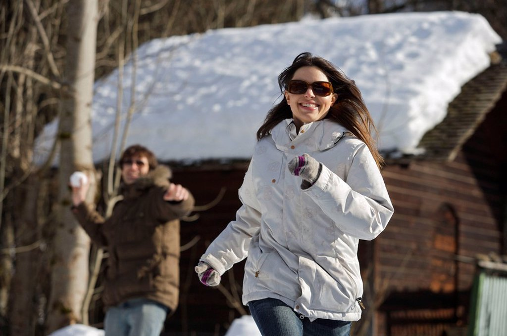 Stock Photo: 1773-21498 Couple in casual ski wear throwing snowballs.