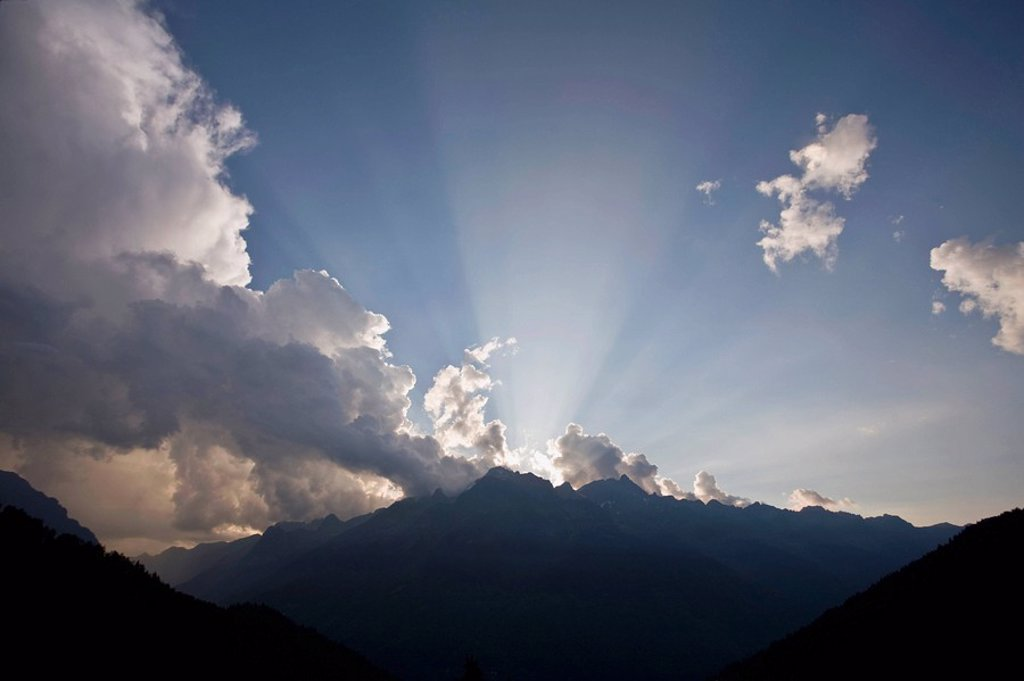 Biblical ray of sunlight piercing the sky over a mountain range.Take at sunset.Belledone moutain chain. Alps,France : Stock Photo