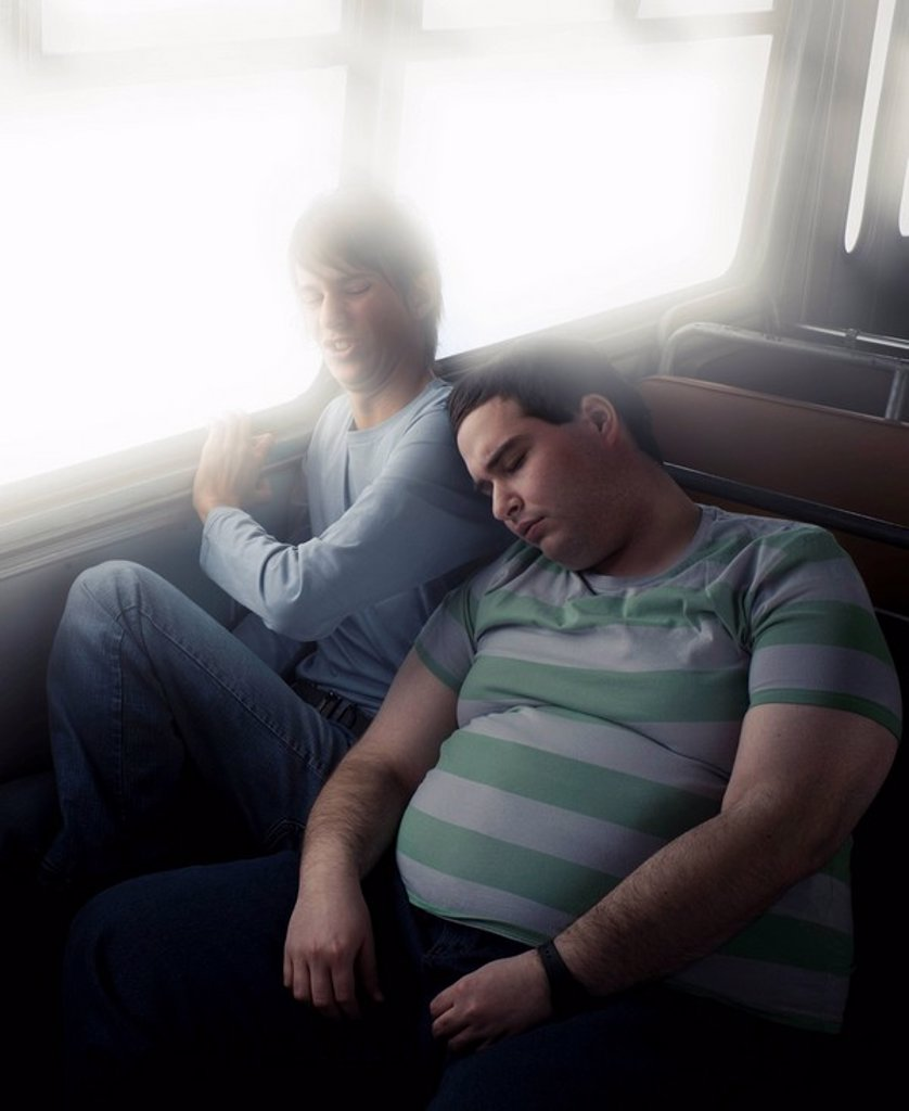 Thin boy squashed by fat boy : Stock Photo