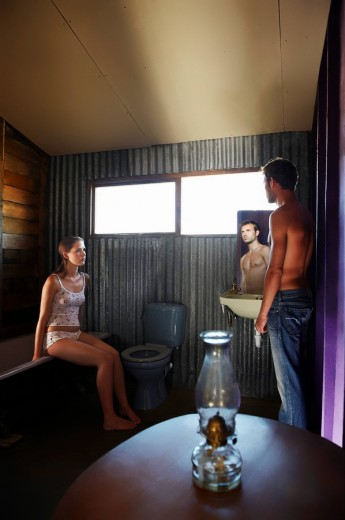 Teenage girl in underwear sitting on edge of bath tub, she is looking at a topless man who is standing looking out of the window. The man is reflected in the mirror. : Stock Photo