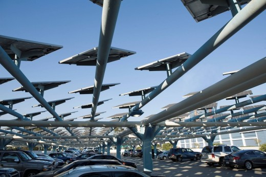 Photovoltaic cell panels, tracking the sun mounted above parking lot to capture solar energy used to generate electricity in urban landscape : Stock Photo