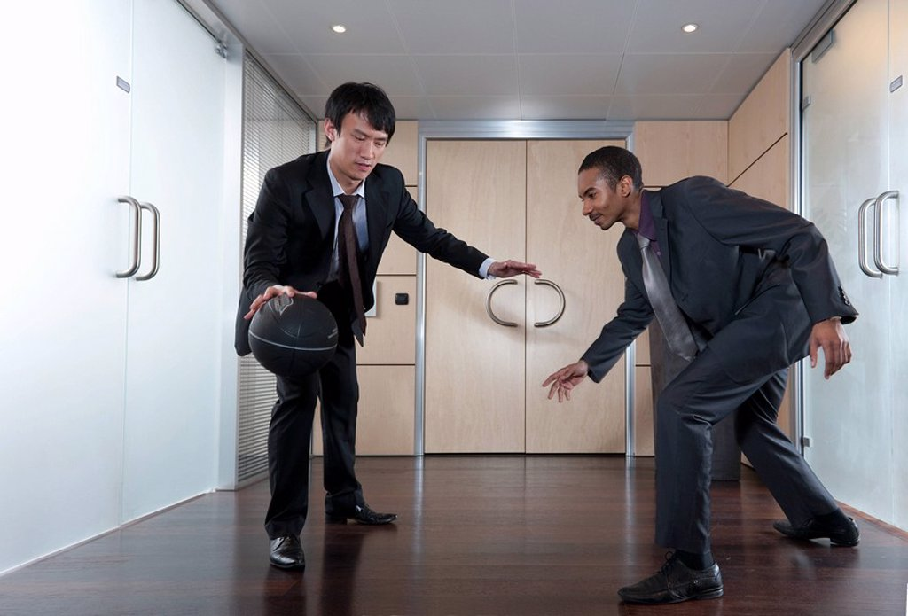 Businessmen playing basketball in office : Stock Photo