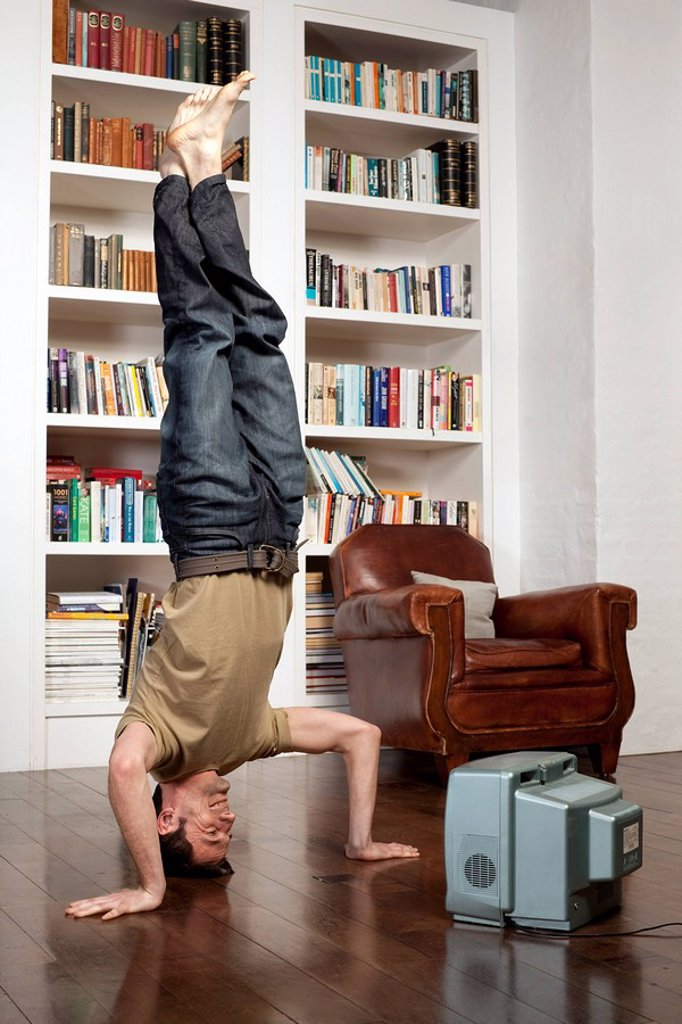 Stock Photo: 1773-25351 man standing on head with tv