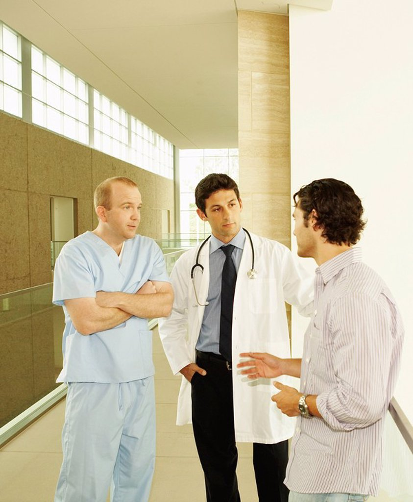 Stock Photo: 1773-27193 Doctor and nurse, wearing scrubs and lab coat, standing in hallway discussing care with patient or patient´s family in modern hospital or clinic