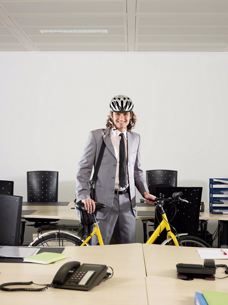 Man with bicycle in office : Stock Photo