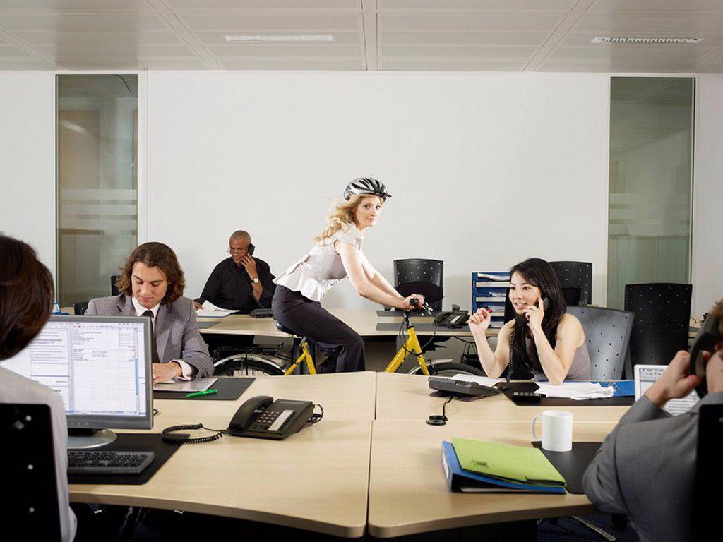 A girl cycles through an office : Stock Photo