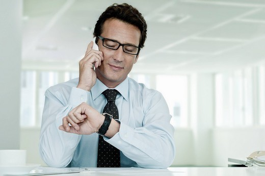 Businessman on phone looking at watch : Stock Photo