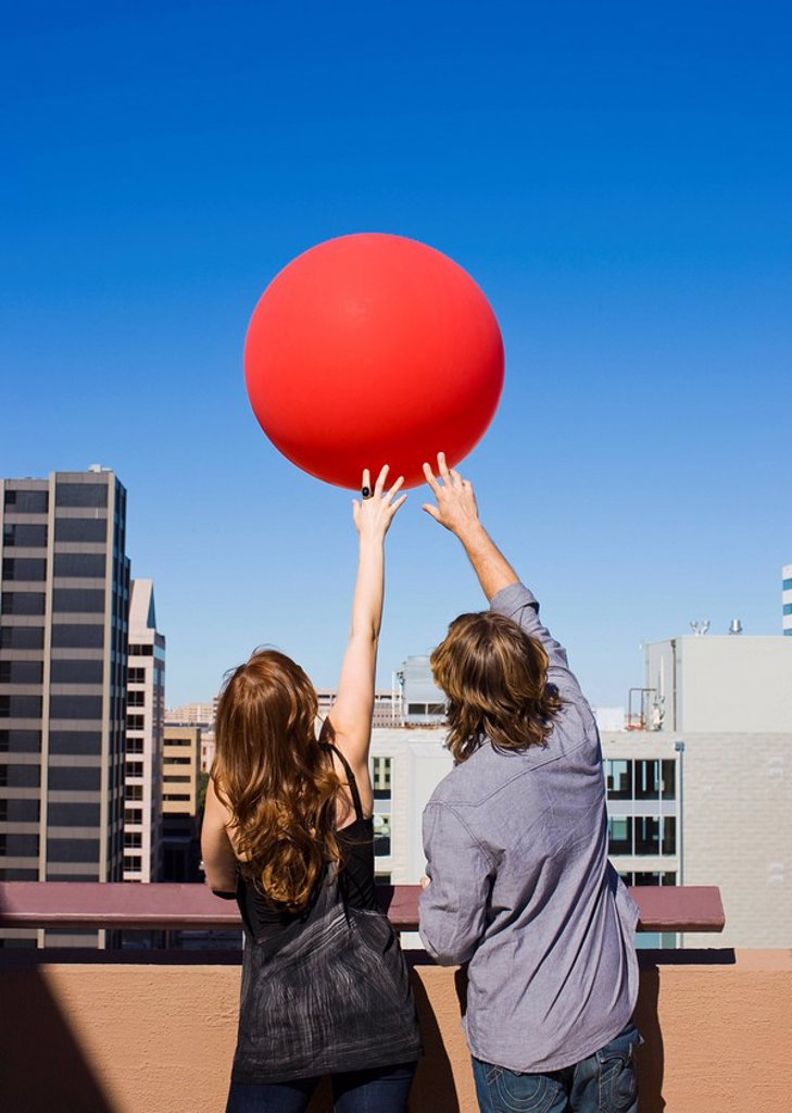 Stock Photo: 1773-28489 friends on roof top with red balloon