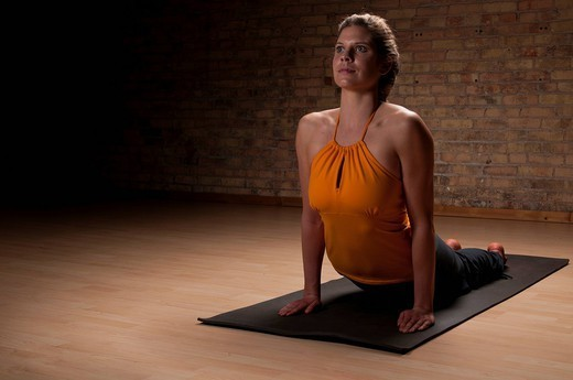 Woman practicing yoga on mat : Stock Photo