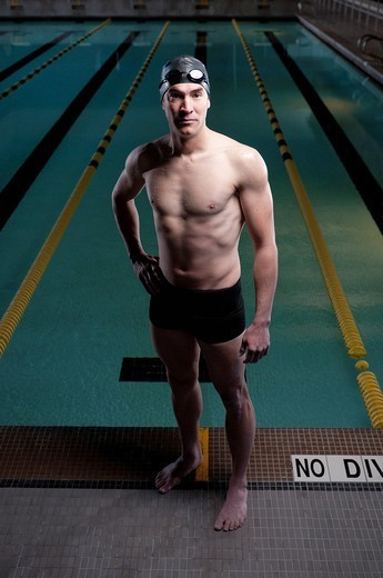 Swimmer standing by swimming pool : Stock Photo