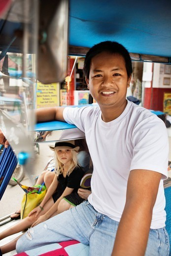 Smiling pedicab driver with passengers : Stock Photo