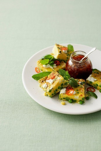 Plate of quiche with peas and tomatoes : Stock Photo